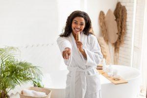 African American Woman Having Fun Singing With Hairbrush In Bathroom
