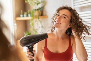 Happy smiling woman using hair dryer in bathroom