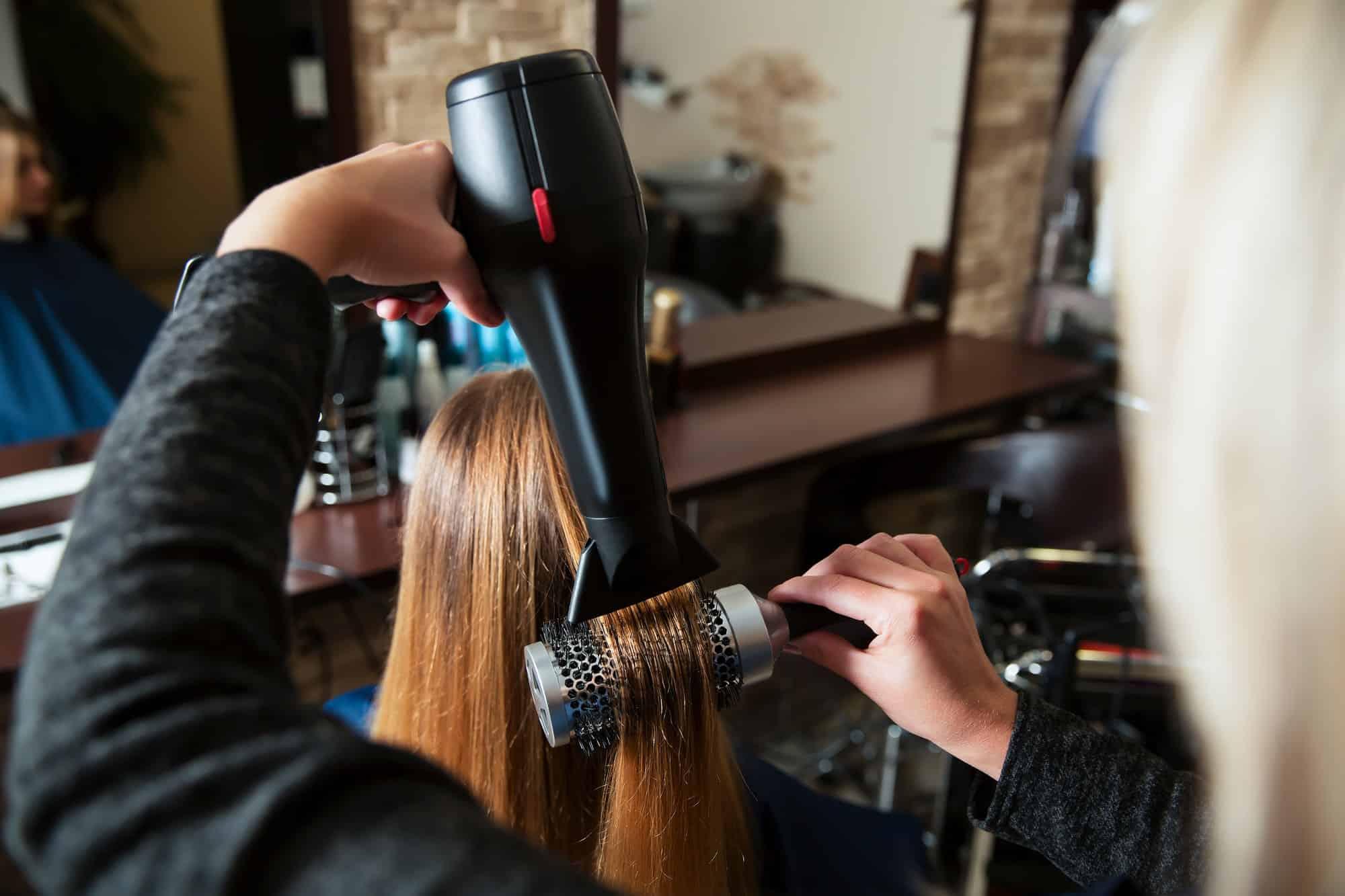 Making hairstyle using hair dryer.